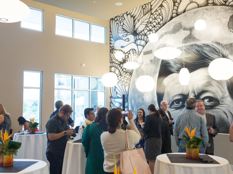 Attendees gather in a large common room with a large mural painted by Los Otros.