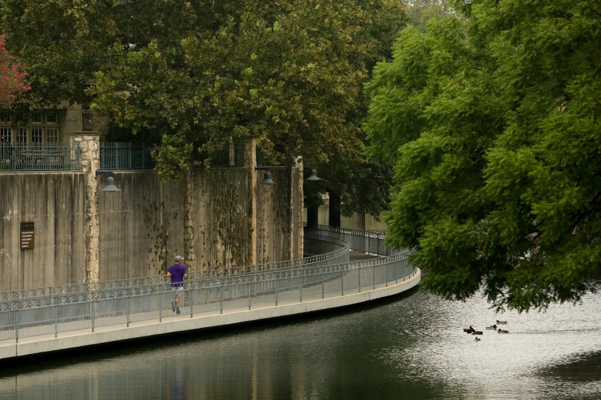 A jogger runs along the San Antonio River near the San Antonio River Authority headquarters in the King William Historic District.