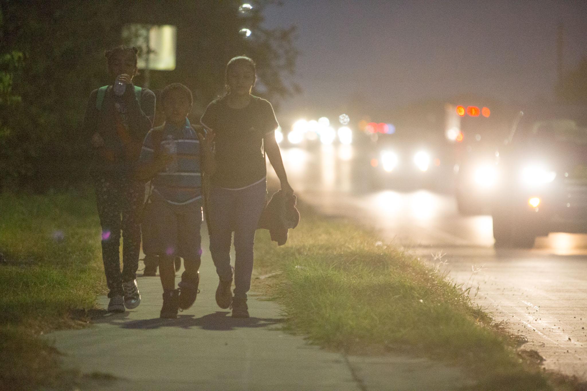 Students of Hutchens middle school Navyih Herrera, Rosalynn Gonzalez, and Chad Herrera, walk along Zarzamora Street during their morning commute to morning class.