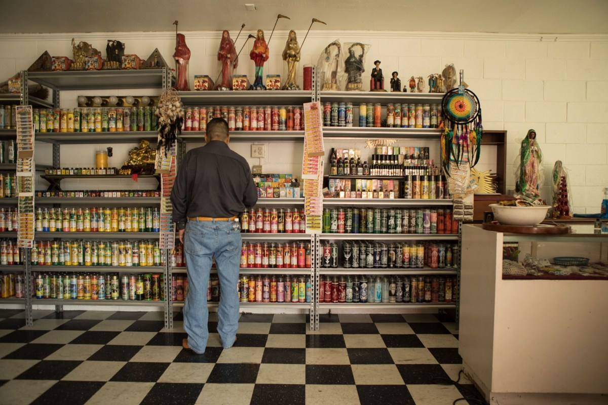 A man explores the candle offerings of Botanica Obadina.