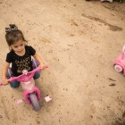 Daniella Zapata, 1, rides a play motorcycle outside at the SJRC Texas Pregnant Parenting Teen Program.