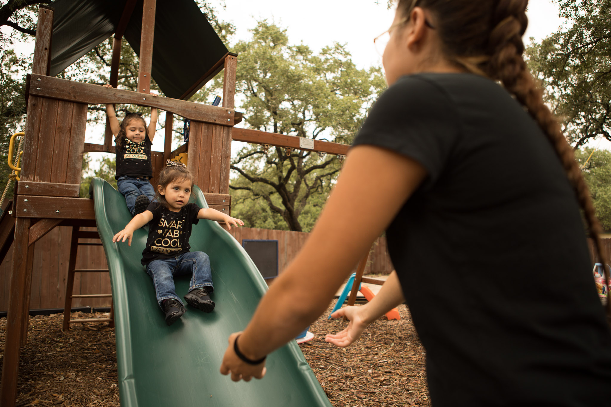 Briana Zapata, 17, (right) holds out her arms at the bottom of the slide to catch her daughters (from left) Natalie, 3, and Daniella, 1, at the SJRC Texas Pregnant Parenting Teen Program.
