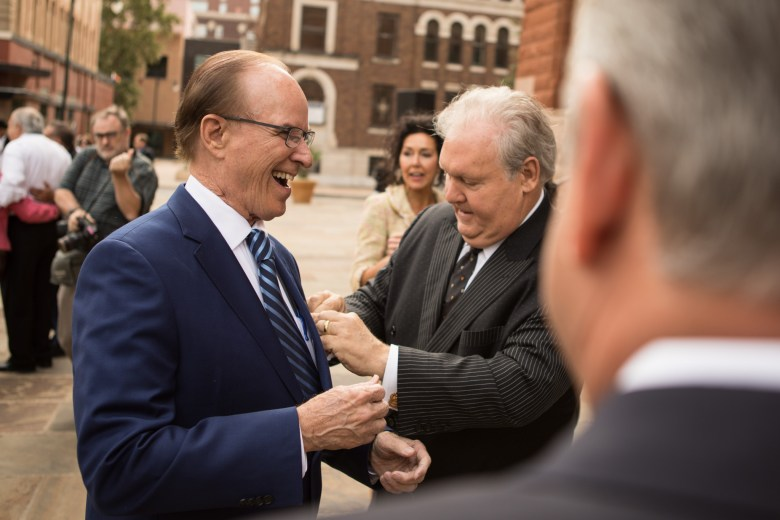 (From right) Mission Park Funeral Chapels and Cemeteries Chairman and CEO Dick Tips places a handkerchief into the pocket of Bexar County Judge Nelson Wolff before Wolff's campaign announcement in front of Bexar County Courthouse.