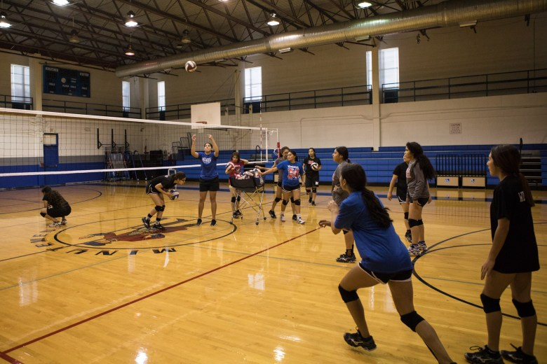 Memorial High School Volleyball Coach Samantha Mendez serves the ball during practice.