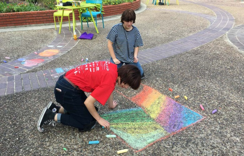 Henry Ford Academy students prepare a rainbow of color for Saturday's Artpace Chalk It Up free community event during the press announcement at Travis Park.