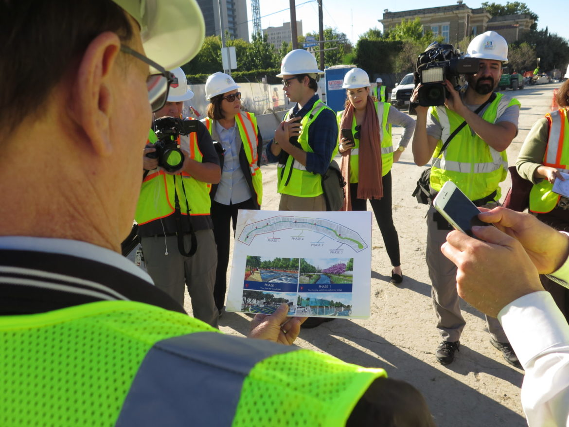 Bexar County Judge Nelson Wolff compares renderings to the construction site of the San Pedro Creek Improvements Project.