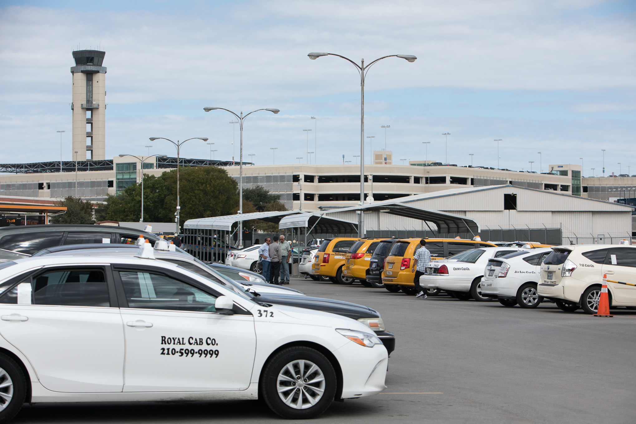Taxi vehicles line parking spaces at the airport orange lot.