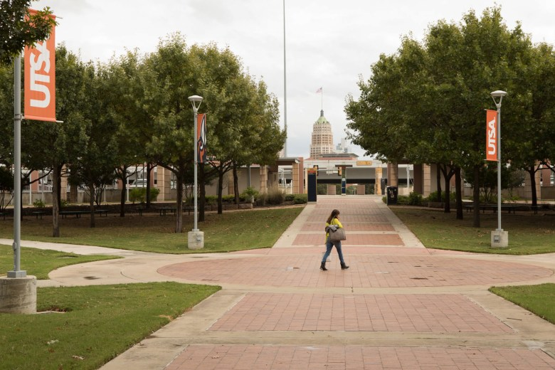 A woman walks through UTSA Downtown Campus with downtown visible through the trees.