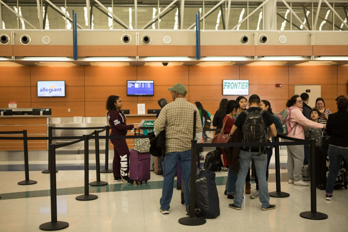 Travelers wait to check luggage in San Antonio International Airport on the day before Thanksgiving.