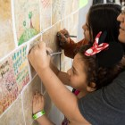 (From left) Zoe Garza, 7, Kyra Garza, 11, and Vicky Garza sign the Wall of Hope for austism awareness at AccessAbility Fest.
