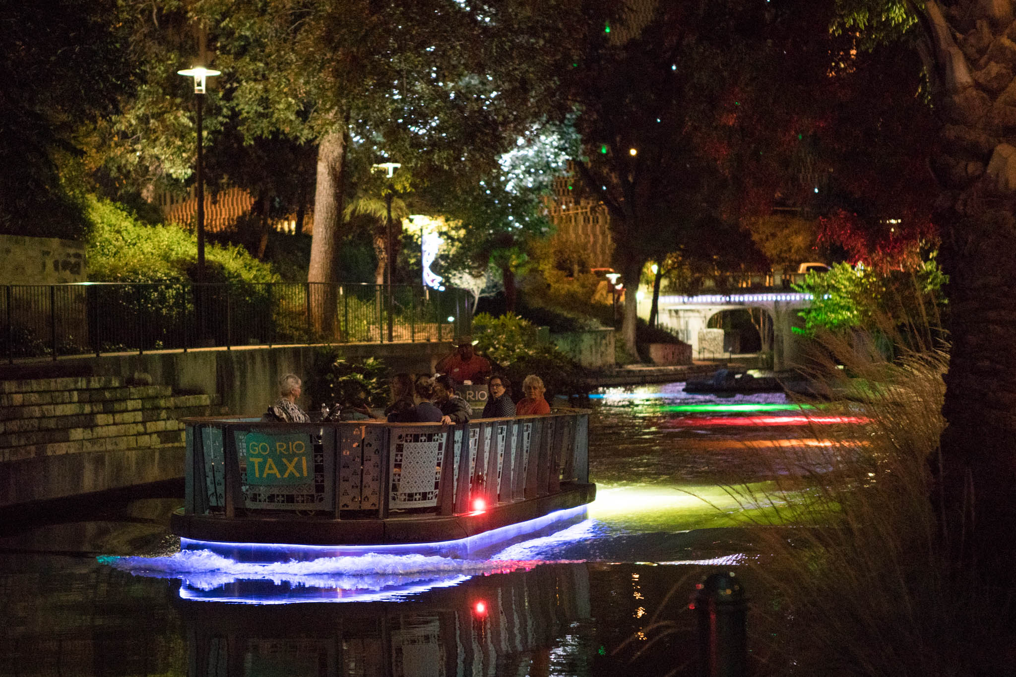 A new San Antonio River Barge passes over the holiday-covered spotlights along Museum Reach.