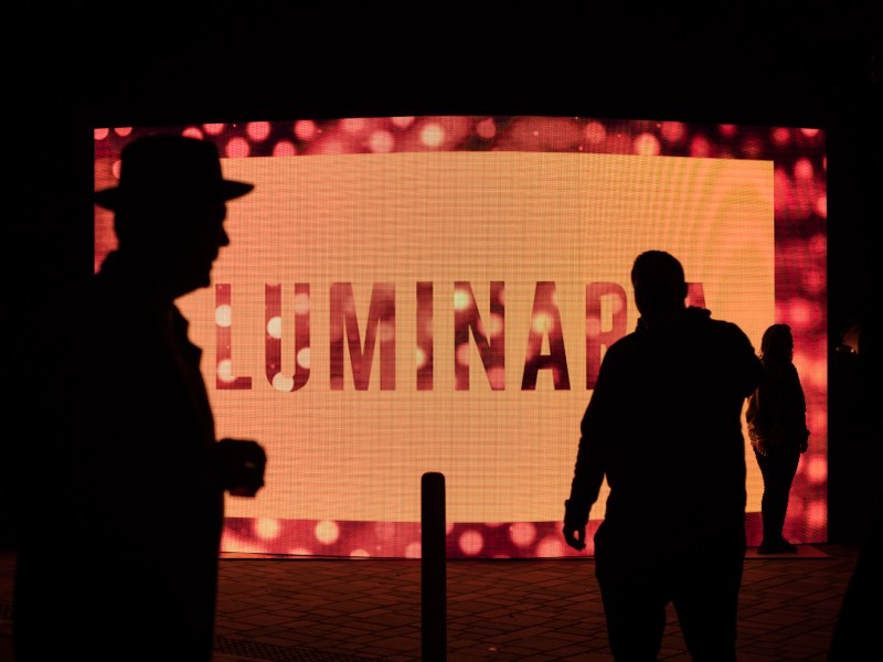 Silhouettes walk in front of the Luminaria sign at Hemisfair Park.