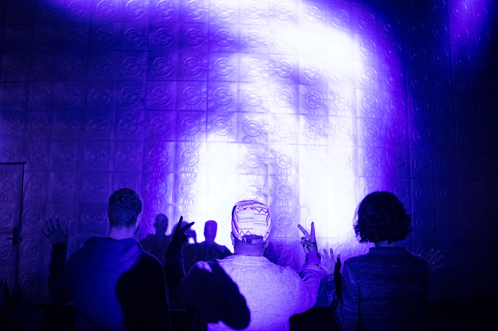 (From left) Chris Stokes, Olivia Youngblood, and Stephanie Marquez make shadow puppets in front of a light display at Luminaria.