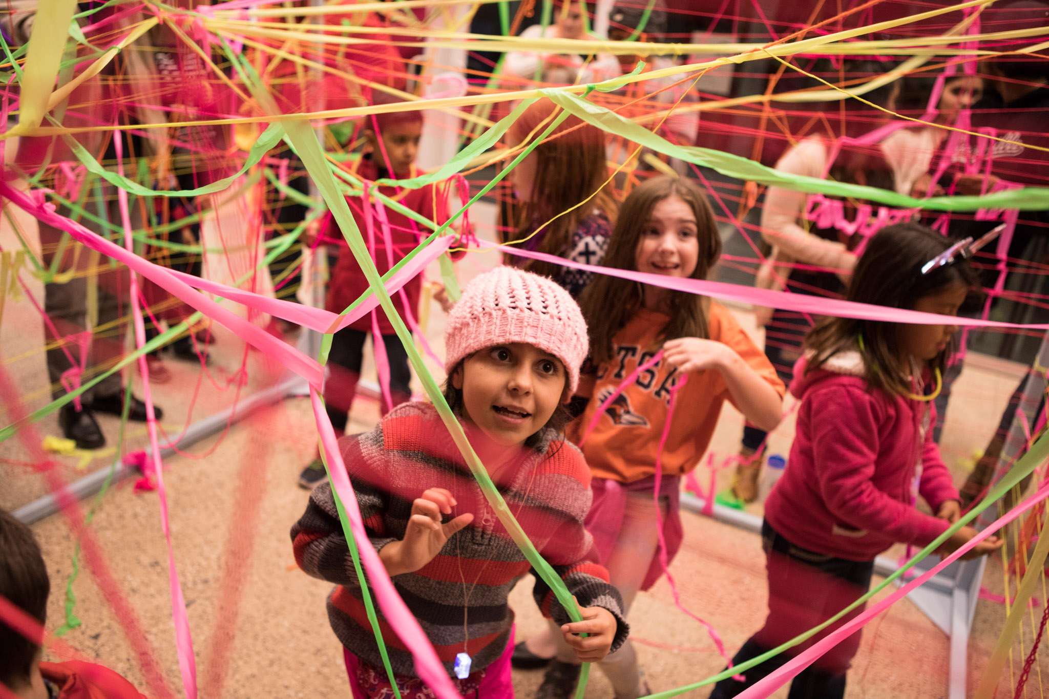 """Christine Gonzales, 9, concentrates on tying colored strings in the art piece """"Cube Loom"""" by Katie Pell at Luminaria."""