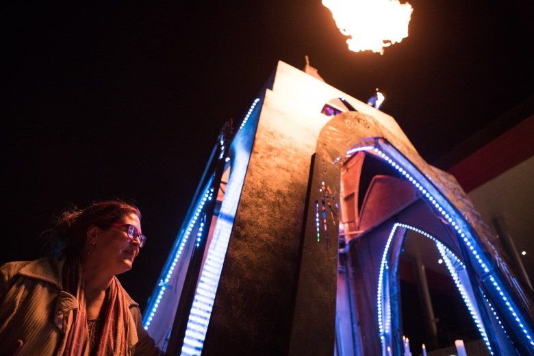 """Women Who Weld's Kathleen Keahey presses a button to ignite a flame at the top of """"Temple Trip"""" at Luminaria."""