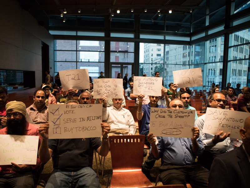 Local store owners hold up signs opposing the campaign calling for a city ordinance to raise the legal age for the sale of tobacco products from age 18 to age 21 at the Tobacco 21 Town Hall Meeting.