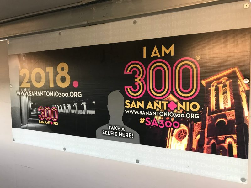 A Tricentennial billboard is displayed in the walkway from the parking garage at the San Antonio International Airport.