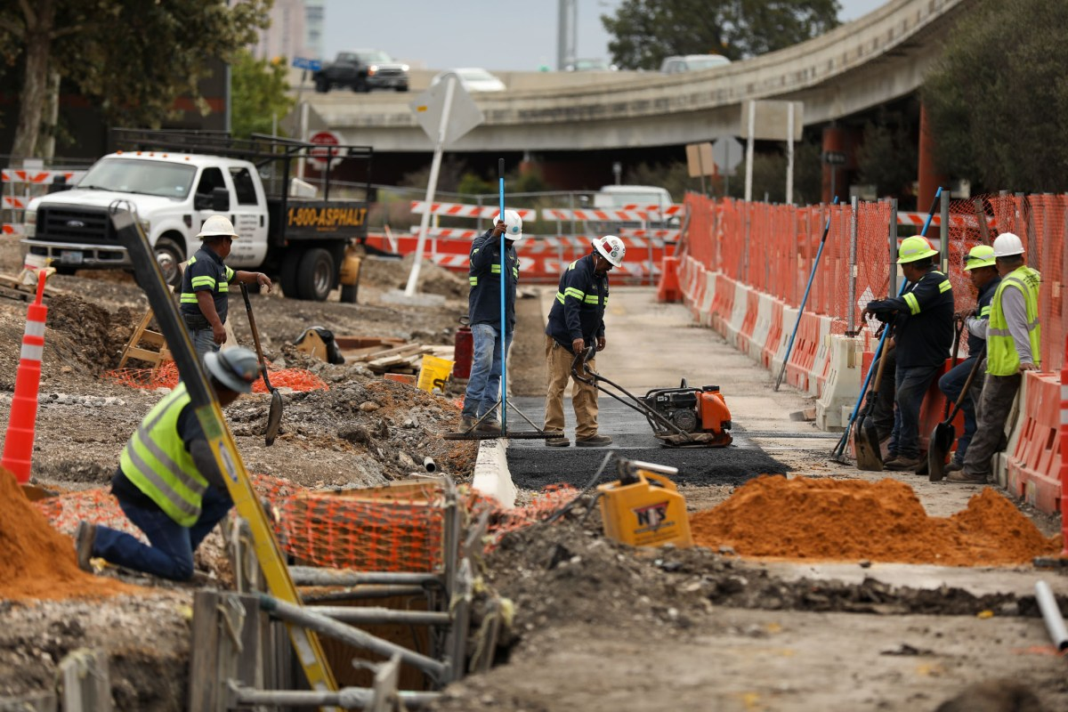 Construction crews work to reconstruct a street with a protected bike and pedestrian path along Avenue B near the Pearl.