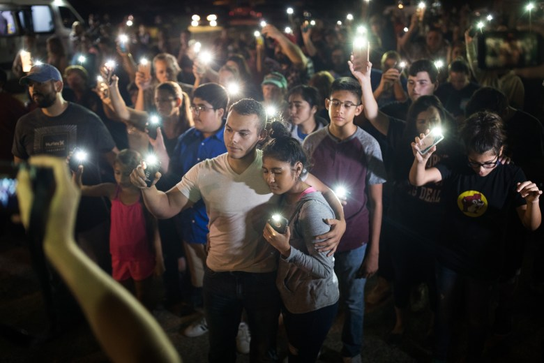 Matthew Mata and Erika Gonzalez (center) embrace as they hold their light emitting phones during the vigil at Sutherland Springs.