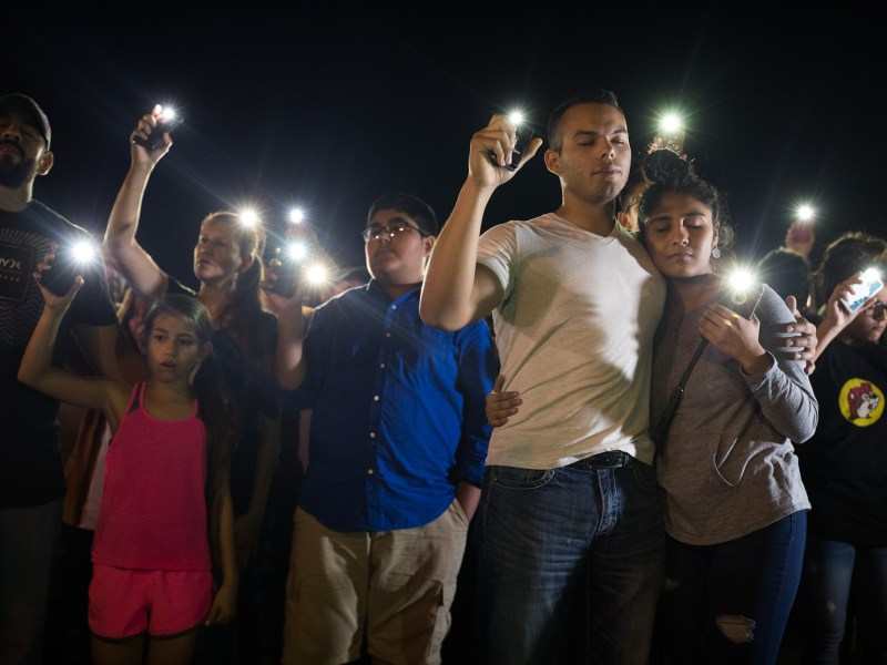 Sutherland Springs residents Matthew Mata and Erika Gonzalez embrace as they hold their light emitting phones during the vigil at Sutherland Springs.