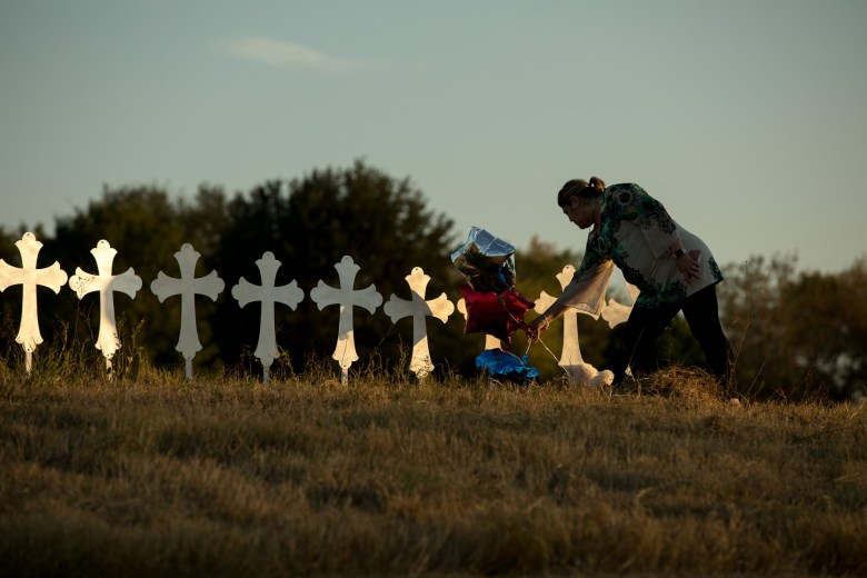 Pastor of Believers Christian Fellowship Laura Torres adjusts balloons that are left at a cross among the 25 others at Sutherland Springs.