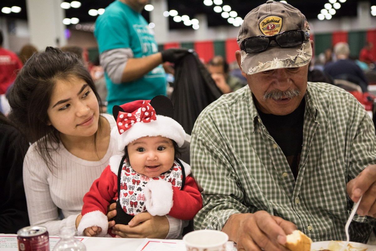 (From left) Rosale Salazar, 15, Mia Luna, 4 mo., and Leonard Sanchez enjoy their meals at the 25th annual H?E?B Feast of Sharing holiday dinner.