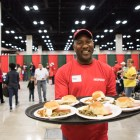H-E-B partner Bobby Sims serves meals at the 25th annual H?E?B Feast of Sharing holiday dinner.