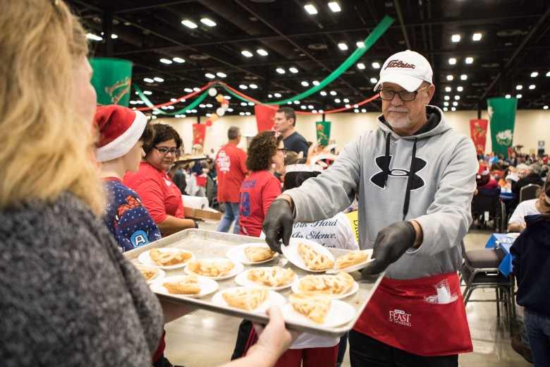 Dean Dooms distributes apple pie at the 25th annual H?E?B Feast of Sharing holiday dinner.