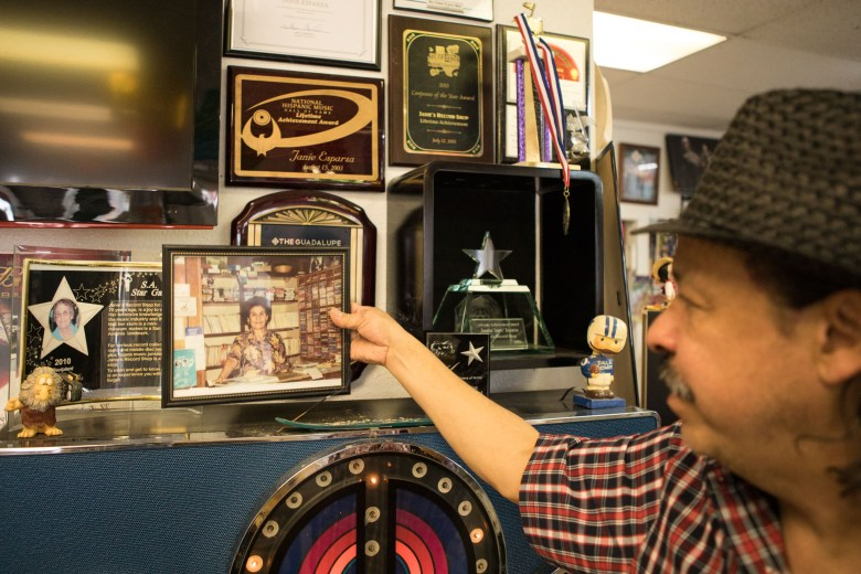 Robert Esparza holds up a photo of his mother Janie Esparza in the earlier days of her founding of Janie's Record Shop.