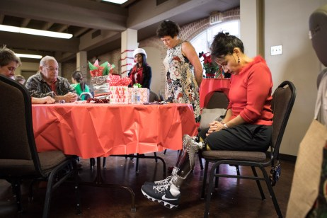 Yvonne Llanes (right) bows her head to a prayer led by Stephanie Richardson (center) at the San Antonio Amputee Foundation Annual Holiday Luncheon.