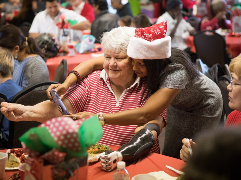 San Antonio Amputee Foundation Founder and Executive Director Mona Patel (right) takes a selfie with Gayle Fisk at the San Antonio Amputee Foundation Annual Holiday Luncheon.