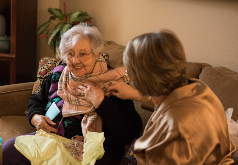 Becky Hoag (right) assists Rose Williams with putting on a new scarf.