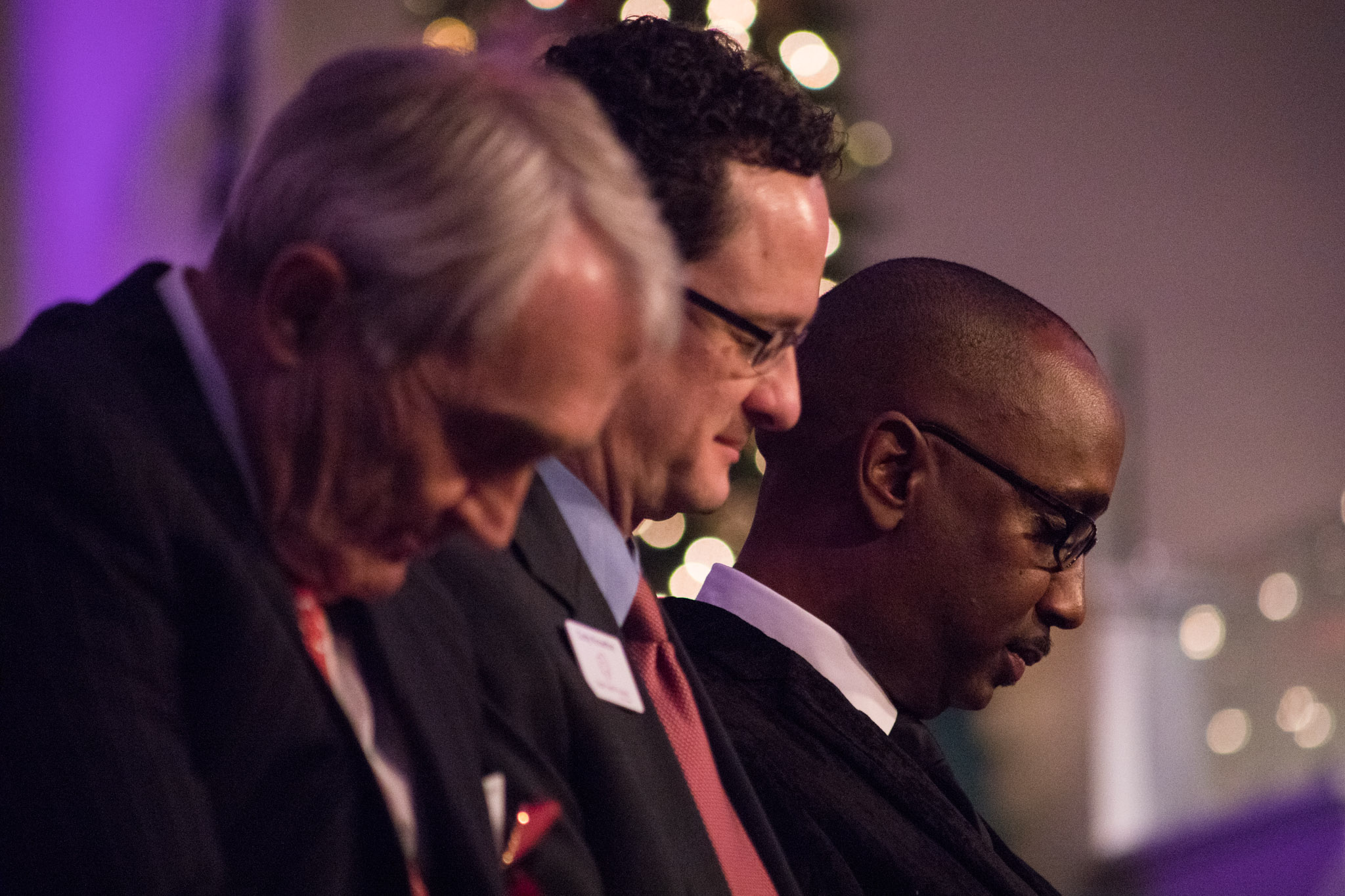(From left) Baptist Health Foundation of San Antonio Chairman of the Board Toby Summers, Baptist Health Foundation of San Antonio President and CEO Cody Knowlton, and Master of Ceremonies Marvin Hurst bow their heads in prayer before the awards ceremony.