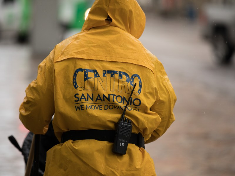 A Centro ambassador makes rounds in front of the Alamo as it rains.