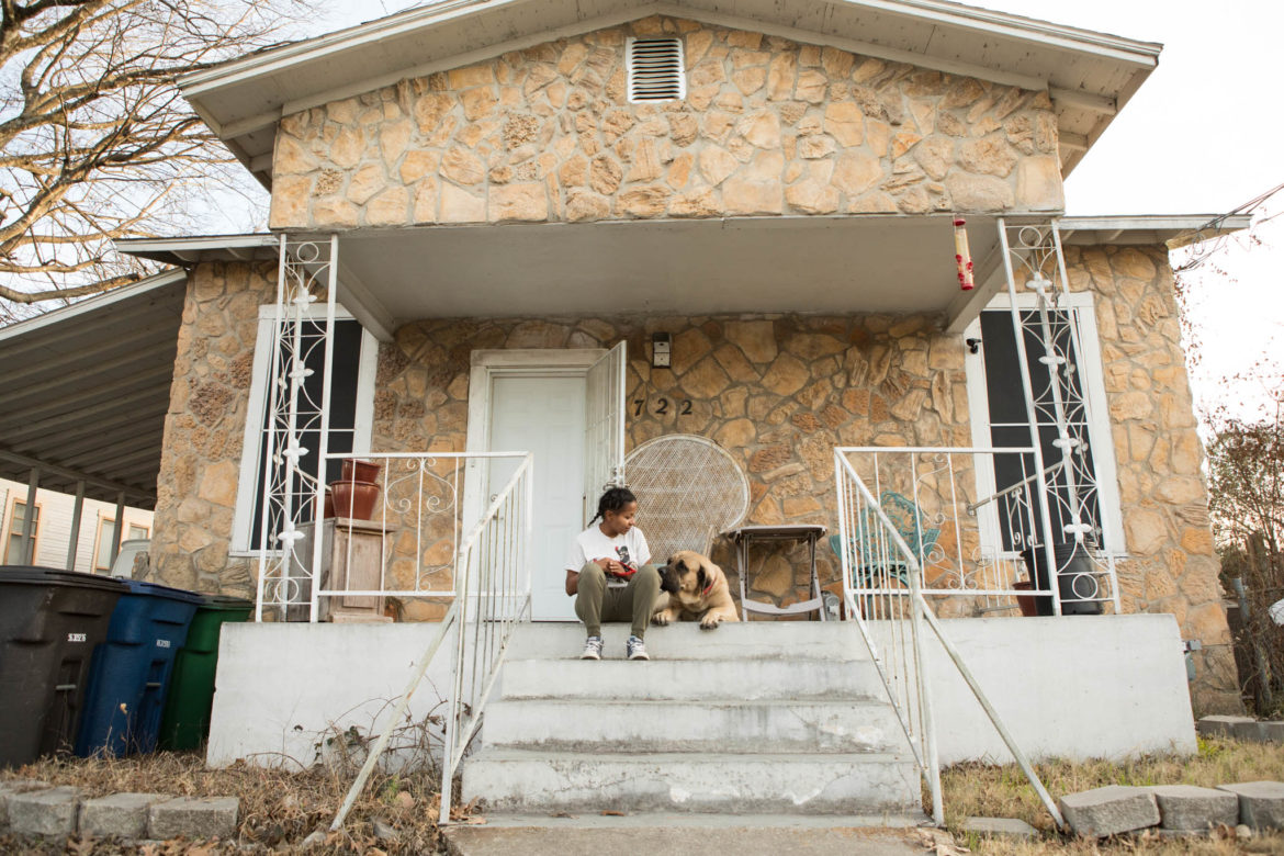 Natasha Bakunda sits with her dog on the front port of her home in Dignowity HIll.