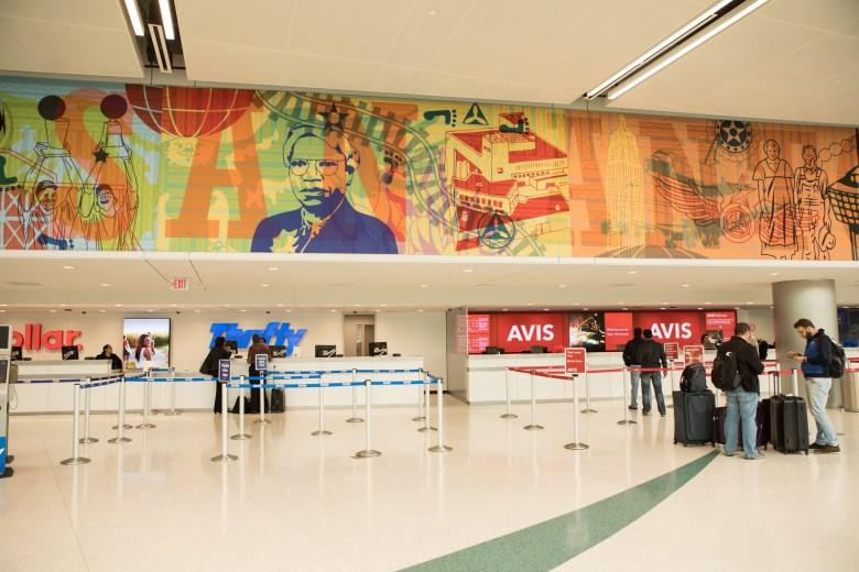 The 240-linear-foot, multi-panel mural '¡Adelante San Antonio!' adorns the walls of the new rental car facility at the San Antonio International Airport.