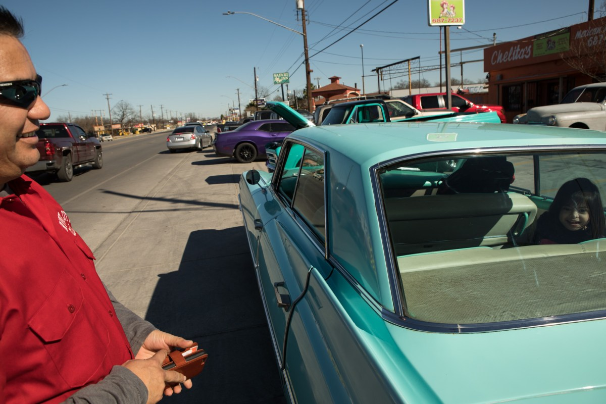 Julio Buelna (left), River City Classics Car Club member, laughs as his daughter Luna Buelna, 7, sits in his 1963 Cadillac in front of Del Bravo Record Shop.