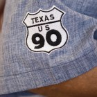 Javier Gutierrez, Del Bravo Record Shop owner, displays his pride for Old Highway 90 on his shirt sleeve.