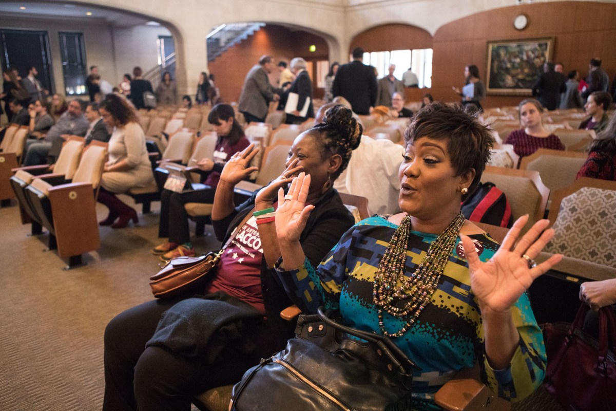 (From right) Dr. Keely Petty and Sharrell Kemp raise their hands and cheer in excitement upon the passing of the Tobacco 21 ordinance.
