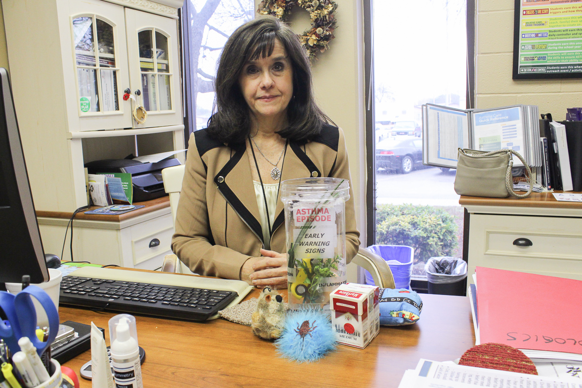 Diane Rhodes, asthma educator for North East Independent School District, sits behind her desk with visual aids she uses to teach children about that triggers asthma attacks.