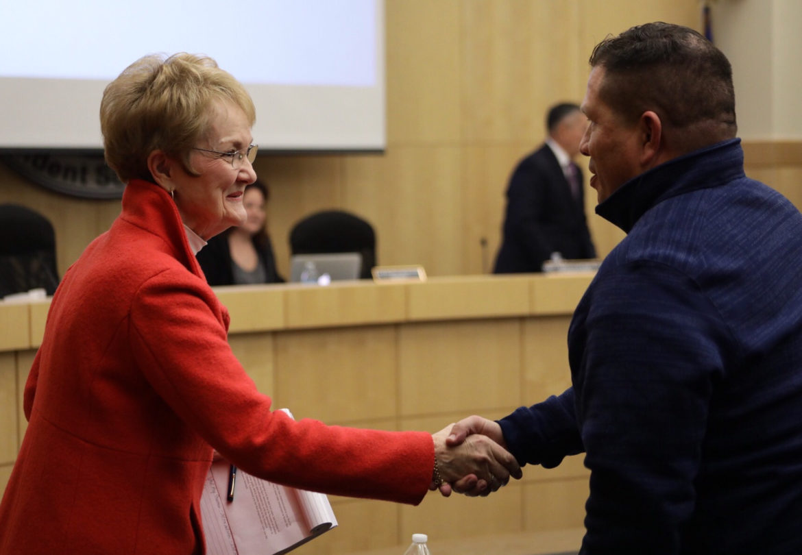 State Conservator Judy Castleberry shakes hands with members of the audience after announcing to the school board that her appointment is coming to an end.