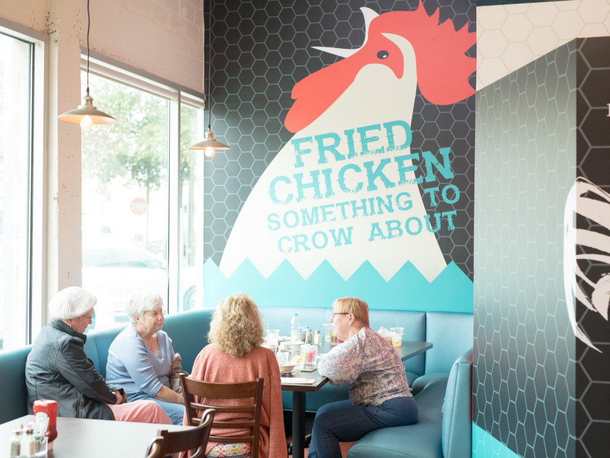 A group of patrons occupy one of the large corner booths at the new location.