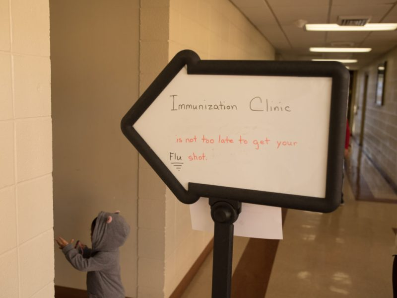 A sign points towards the immunization clinic at the Metro Health Building.