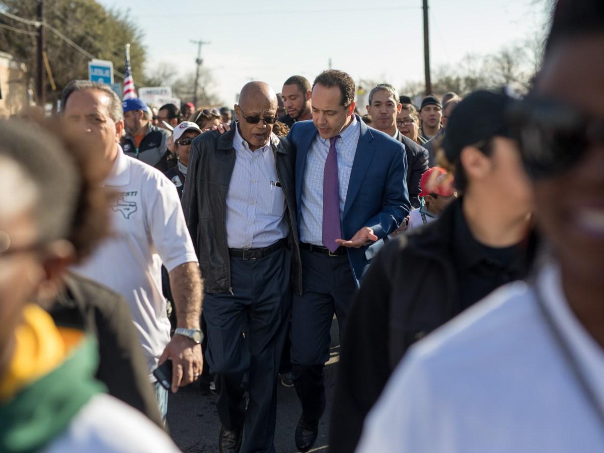 State Senator Jose Menendez (D-San Antonio) walks with Denver McClendon during the march.