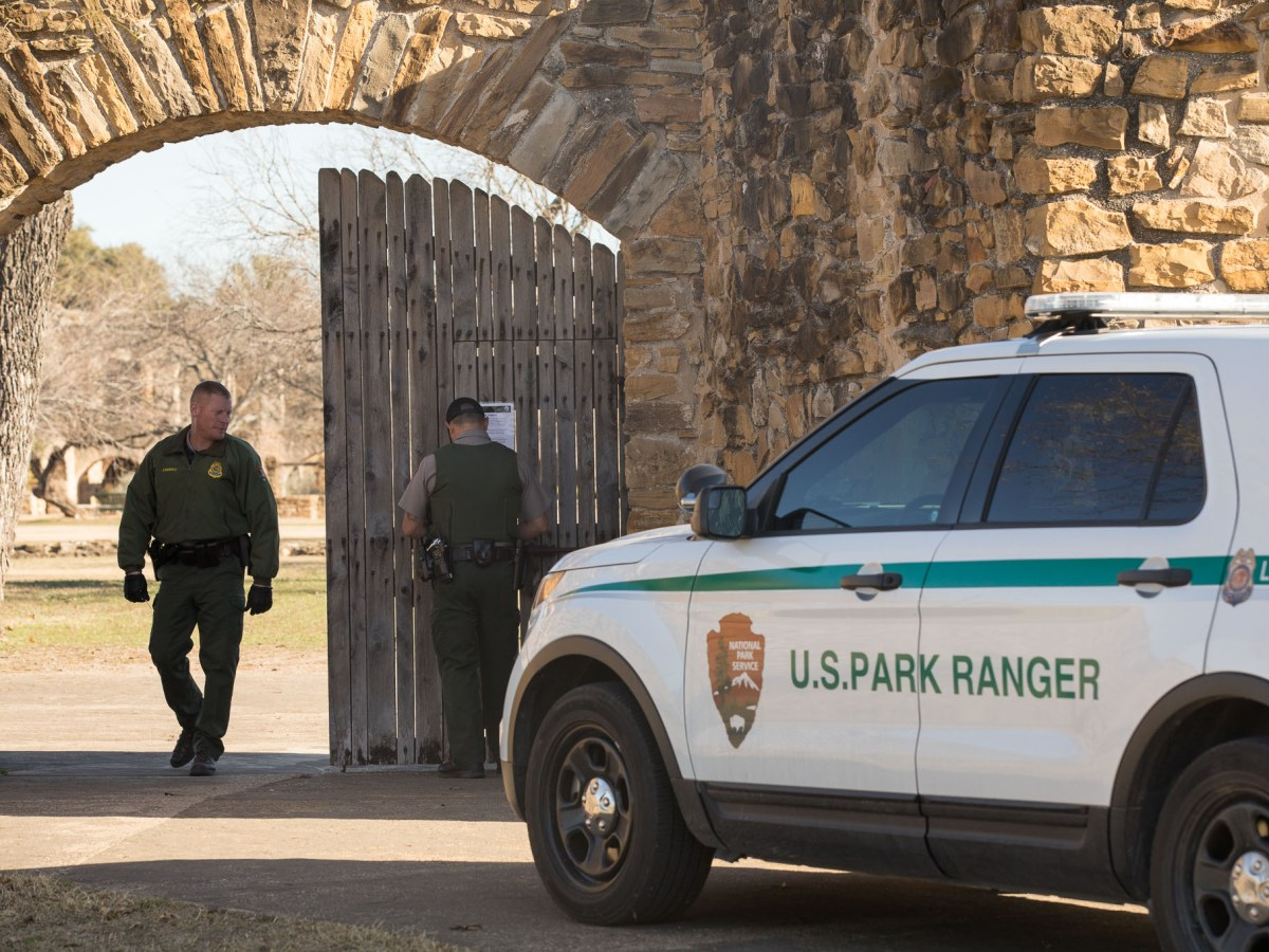 United States Park Rangers open the front gates to Mission San José.