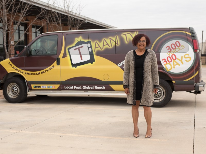 Founder of The African American Network (TAAN) Laura Thompson stands outside the 300 Voices 300 Days van.