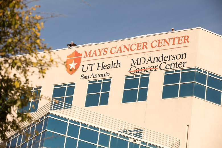 A temporary sign is installed highlighting the Mays Cancer Center name.