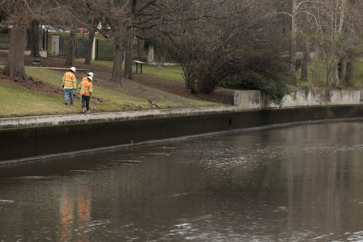 Construction workers walk along the banks of the San Antonio River as the level has been receded for the project.