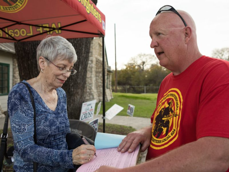 Robin Black (left) signs a petition for chart amendments held by retired fire department lieutenant Bert Kuykendall outside a polling site.