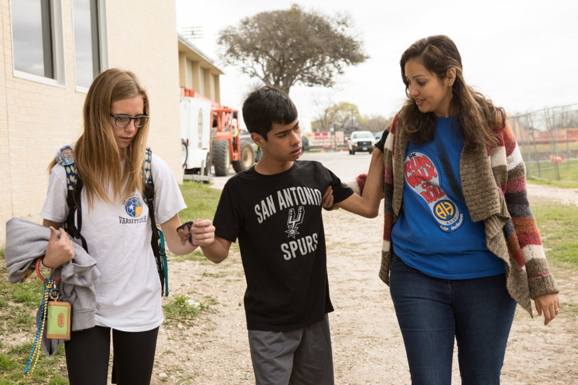 (From left) Jolie Press, Alex Molina, and Unified Champion School Advisor Erika Guerrero walk from one building to another at Alamo Heights High School.